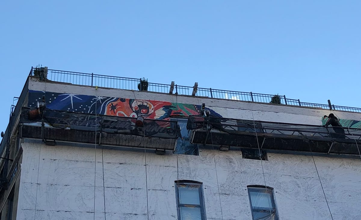 Painters on hanging platforms starting a mural on the side of a building in Manhattan • 'Let's paint the town 'you'' Earnest Agency blog